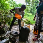 Christine collecting water at a source close to the village. She will carry water using heavy tanks. Bakumba, Cameroon. 2014