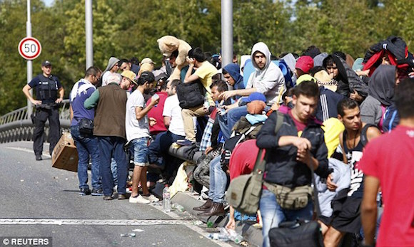 2C6B40CD00000578-3249667-Migrants_and_refugees_line_up_as_they_wait_to_cross_the_border_f-a-111_1443223070501