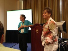 George Koerner, left, and Jann Guthridge stand next to a lectern at the front of a classroom while describing their experiences with Sage Inventory Advisor during a session at Sage Summit 2013.
