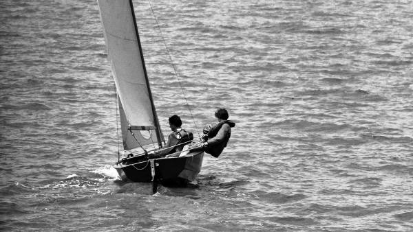 Small sailing boat with two people in.
