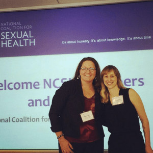 "NSVRC's Jennifer Grove (left) and PreventConnect's Ashley Maier (right) standing and smiling in front of a powerpoint slide projected on a screen that reads ""National Coalition for Sexual Health"""