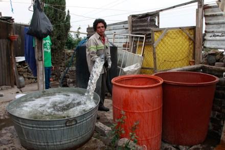 Un hombre rellena de agua una tina en Iztapalapa. Foto: Hugo Cruz