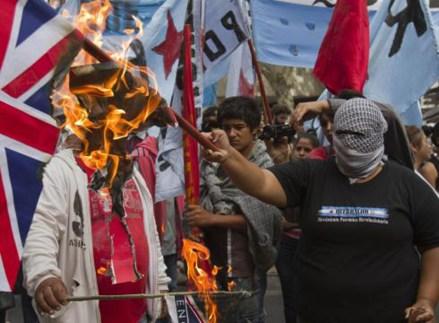 Una mujer quema una bandera inglesa en Argentina. Foto: AP