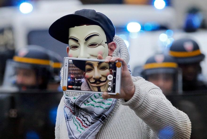 Un activista con una máscara de Guy Fawkes protesta en París. Foto: AP / Christophe Ena