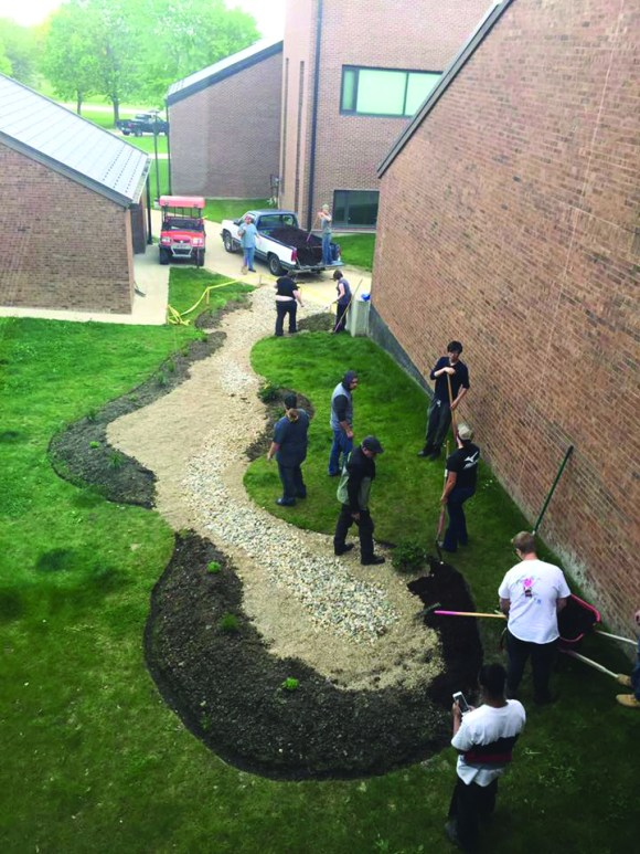 Photo courtesy of Julie Angel | Parkland College Natural Sciences Students in a landscape construction class taught by Kaizad Irani at Parkland College work on a stream model landscape in the L-wing courtyard, which will be the new earth science outdoor lab space.