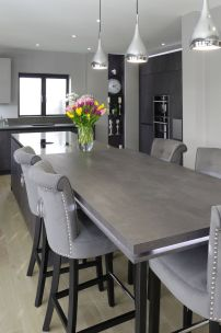 Concrete graphite kitchen with island and breakfast bar connected / secret doors to utility room
