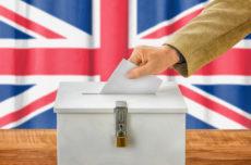 47062863 - man putting a ballot into a voting box - united kingdom