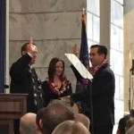 Utah Attorney General Sean Reyes takes the oath of office, administered by Utah Supreme Court Associate Justice Thomas Lee. Saysha Reyes, his wife, holds the Bible.