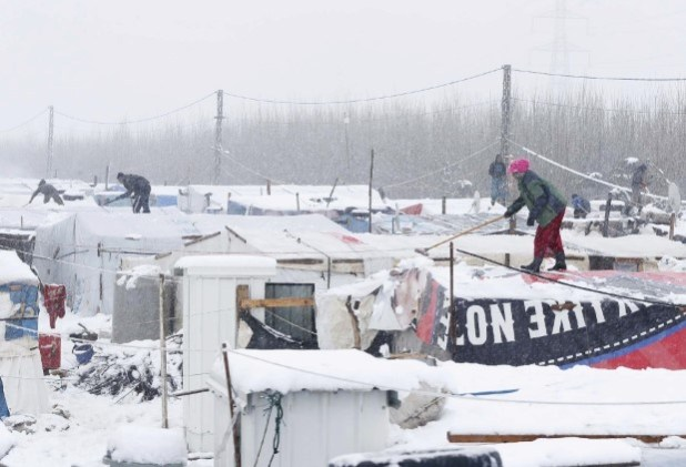 Syrian refugees remove snow from tents during snow fall outside tents at a makeshift settlement in Bar Elias