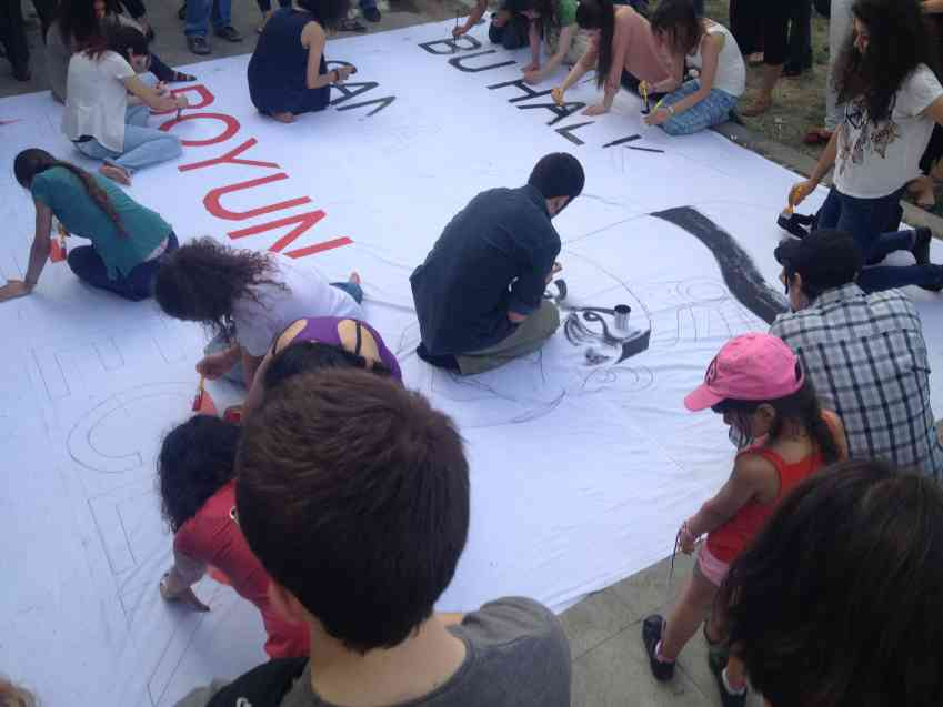 The square is also a site of creative resistance - protestors play music, perform spoken word and paint giant banners.