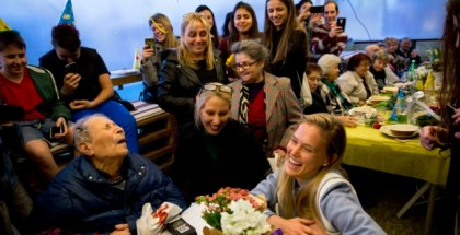 In this Wednesday, Jan. 24, 2017 photo, Israeli Holocaust survivor, Ernest Weiner, foreground left, sits with Israeli supermodel Bar Refaeli, foreground right, during his birthday in a restaurant in the central Israeli city of Ramat Hasharon. More than 100 fellow Holocaust survivors and advocates on their behalf gathered for the 92nd birthday party of Ernest Weiner -- a blind and widowed survivor who uses a wheelchair to get around and still lives on his own. As home to the world's largest survivor community, Israel is grappling to serve the needs of the thousands of people like Weiner who are living out their final days alone. (AP Photo/Sebastian Scheiner)