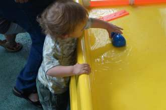 NinjaBaby playing with the water/river table in Kids Central