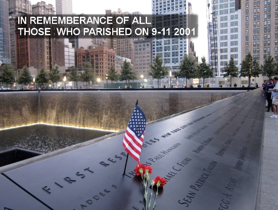 an image of the 9-11 memorial in new york city at the location where the twin towers once stood. the image has the wall surrounding the reflecting pool with the names of the victims carved onto it and a small american flag and red rose placed on the wall and in the background is the water fall filling the pool.