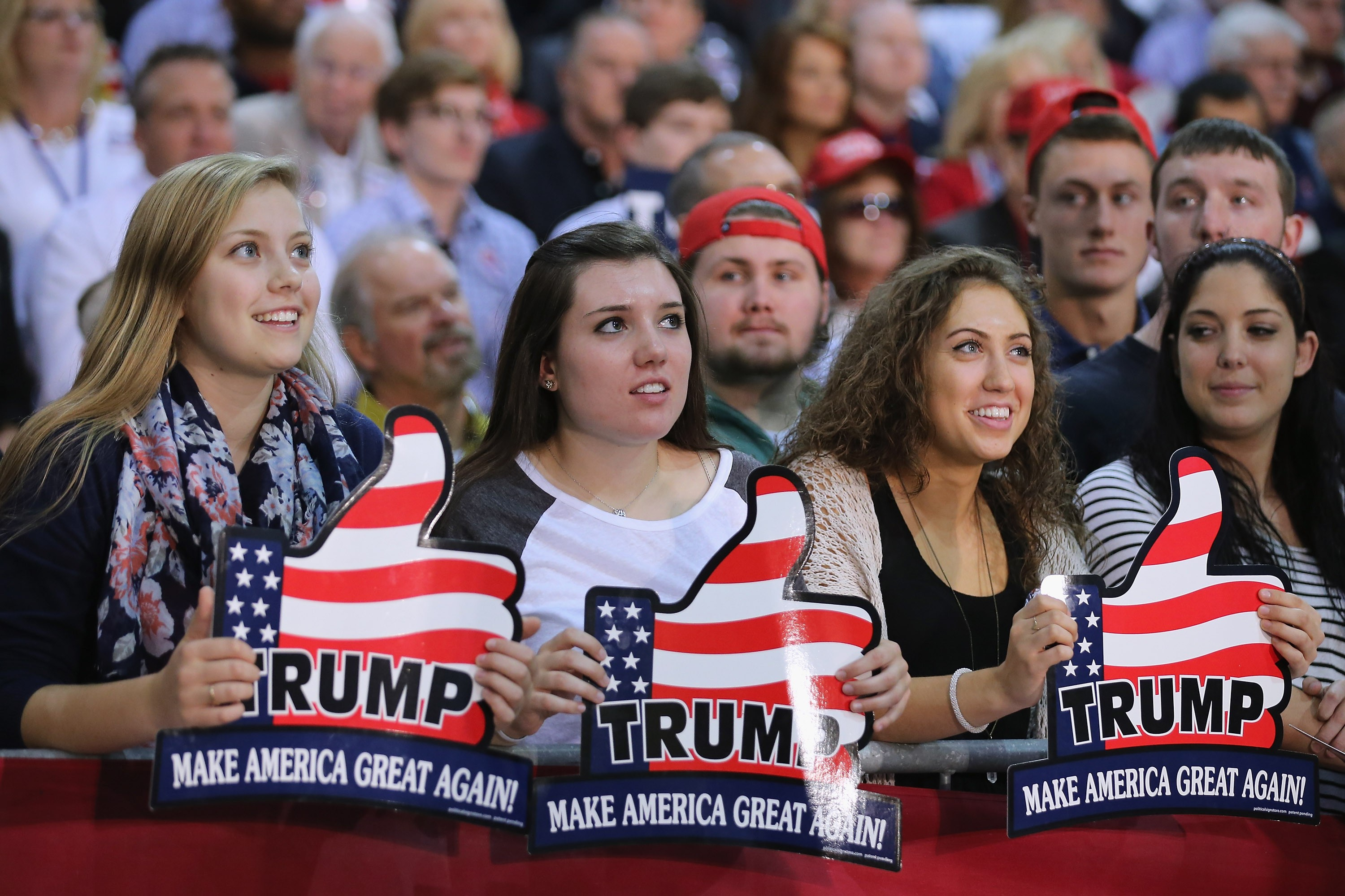 An image of 4 young women trump supporters the look to be in their 20's each is smiling and looking up at President Trump on the stage, each woman is holding a sign in the shape of a thumbs up hand with a U.S. flag background and the signs read