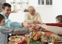 Family Pulling Party Favors During Christmas Dinner --- Image by © Royalty-Free/Corbis