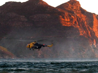 Eric Tollner | About Red Earth Trophies & Sculptures | Photo: Hout Bay, helicopter refilling with water.