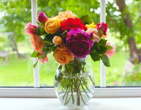 large vase with colorful roses on window sill