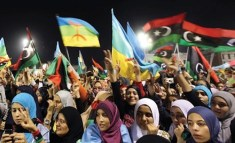 Libyan women waving the new Libyan flag and the flag of the Amazigh people – often called Berbers – during an Amazigh festival in Tripoli, 27 September 2011