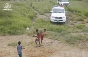 Niños indiferentes a la realidad, juegan pelota.