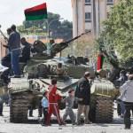 Opositores al régimen de Muamar Gadafi están montados sobre un tanque que tripulan fuerzas contrarias al Gobierno de Libia.