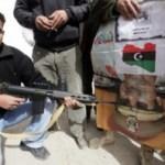 Un manifestante apunta con un arma a un afiche del líder libio.