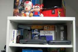 My handheld/controller shelf. Overseen by Mario and Toad.
