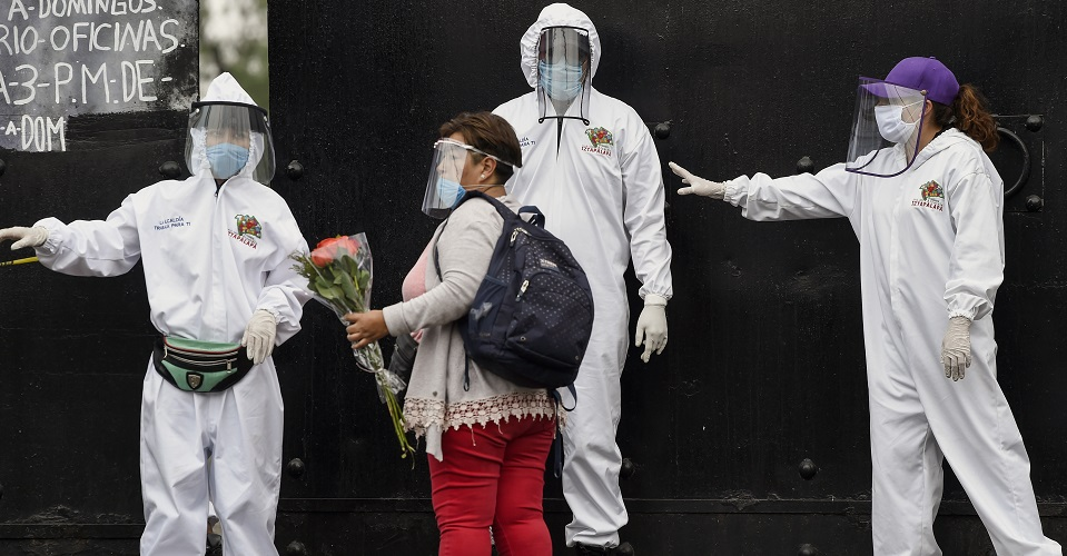 Workers from the Iztapalapa government talk to people trying to enter the cemetery to explain that only are allow two persons at a time outside Pantheon of San Lorenzo Tezonco in Mexico City, on May 14, 2020. (Photo by ALFREDO ESTRELLA / AFP)