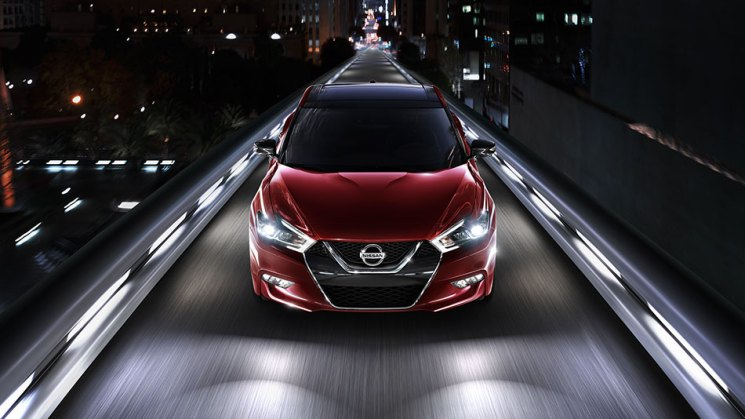 2016-nissan-maxima-coulis-red-front-aerial-view-night-driving-large