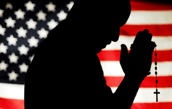PHOTO ILLUSTRATION OF MAN HOLDING ROSARY WITH U.S. FLAG IN BACKGROUND