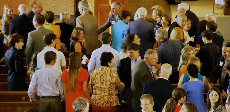 Several former PAG chairs and their families attend the annual Mass. Here, the congregation exchanges a sign of peace.