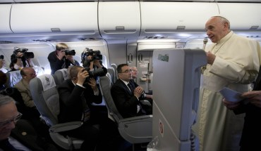 Pope Francis greets journalists aboard the papal flight on his way to Amman, Jordan on May 24, 2014. Pope Francis arrived in Jordan at the start of a Middle East tour aiming to boost ties with Muslims and Jews as well as easing an age-old rift within Christianity itself. AFP PHOTO/POOL/ANDREW MEDICHINI