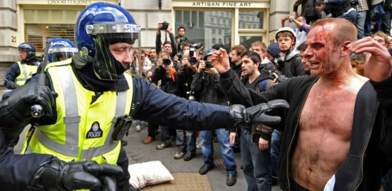 A policeman (L) in riot clothing, restrains a bloodied protestor near the Bank of England, in London, on April 1, 2009. Leaders wrangled Wednesday on how a G20 London summit could fix the global economy as demonstrators attacked a bank in an anti-capitalist riot in the British capital's main financial district. AFP PHOTO/CARL DE SOUZA