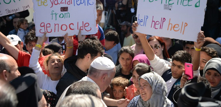 Pope Francis greets migrants and refugees at the Moria refugee camp on April 16, 2016 near the port of Mytilene, on the Greek island of Lesbos. Pope Francis received an emotional welcome today on the Greek island of Lesbos during a visit aimed at showing solidarity with migrants fleeing war and poverty.  Pope Francis, Orthodox Patriarch Bartholomew and Archbishop Jerome visit Lesbos today to turn the spotlight on Europe's controversial deal with Turkey to end an unprecedented refugee crisis.  AFP PHOTO POOL / FILIPPO MONTEFORTE / AFP PHOTO / POOL / FILIPPO MONTEFORTE
