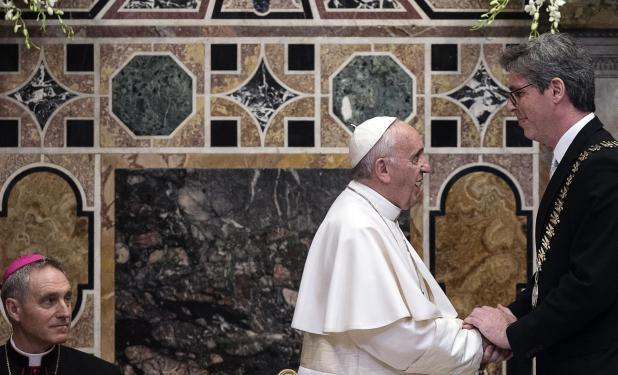 """Pope Francis greets the mayor of Aachen Marcel Philipp during the ceremony where he was awarded the International Charlemagne Prize of Aachen (Karlspreis) at the Vatican, Friday, May 6, 2016. Pope Francis, accepting the prize for promoting European unity on Friday bemoaned that the continent's people """"are tempted to yield to our own selfish interests and to consider putting up fences."""" (Angelo Carconi/Pool photo via AP)"""