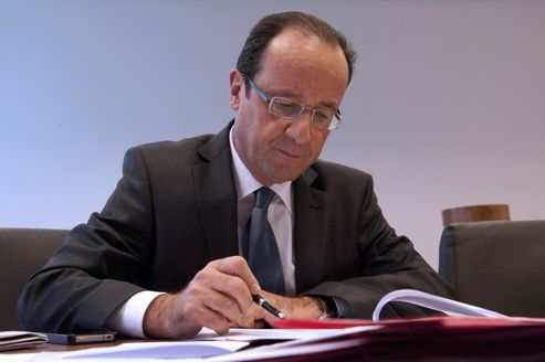 Socialist Party (PS) candidate for the 2012 French presidential election, Francois Hollande, writes down notes during a meeting on February 13, 2012 at the campaign headquarters in Paris.    AFP PHOTO JEAN-FRANCOIS MONIER