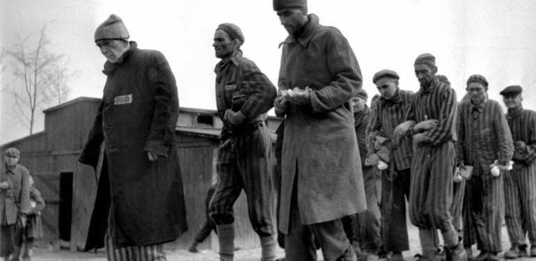 Weak and ill survivors of the Nazi concentration camp in Buchenwald march April 1945 towards the infirmary, after the liberation of the camp by Allied troops.  The man in foreground is General Audibert, an officer in the French Army and member of the French resistance. The construction of Buchenwald camp started 15 July 1937 and was liberated by US General Patton's army 11 April 1945. Between 239,000 and 250,000 people were imprisoned in this camp. About 56,000 died among which 11,000 Jews. On the 5th of April Patton's army liberated the Buchenwald commandos in Ohrdruf. A few thousand Russian and Hungarian Jews, and gypsies were then miserably evacuated from the main camp Buchenwald by the Germans to camps such as Dachau and Fl?ssenburg. On the 11th of April the International Committee (created in August 1943 by the prisoners), who managed to obtain and hide arms during previous shelling, gave the order for an insurrection which pave the way for the US army.  (FILM) AFP PHOTO ERIC SCHWAB AFP PHOTO AFP/ERIC SCHWAB/lab/ls  (Photo credit should read ERIC SCHWAB/AFP/Getty Images)