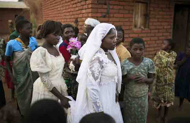 MPHANDULA, MALAWI - AUGUST 19: Suzana Nabanda, age 16, walks with her sister and relatives after a marriage ceremony on August 19, 2006 in Mphandula village, about 30 miles outside Lilongwe, Malawi. She just got married to a farmer a few hours earlier. Mphandula is a poor village in Malawi, without electricity or clean water. Nobody owns a car or a mobile phone. Most people live on farming. About 7000 people live in the village and the chief estimates that there are about five-hundred orphans. Many have been affected by HIV/Aids and many of the children are orphaned. A foundation started by Madonna has decided to build an orphan center in the village through Consol Homes, a Malawi based organization. Raising Malawi is investing about 3 million dollars in the project and Madonna is scheduled to visit the village in October 2006. Malawi is a small landlocked country in Southern Africa without any natural resources. Many people are affected by the Aids epidemic. Malawi is one of the poorest countries in the world and has about 1 million orphaned children.  (Photo by Per-Anders Pettersson/Getty Images)