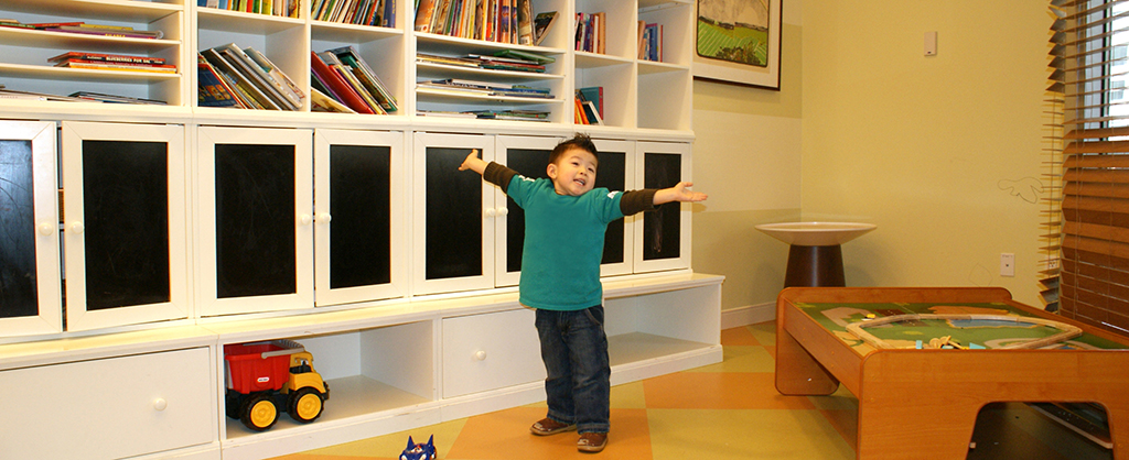 Boy with arms stretched in a playroom