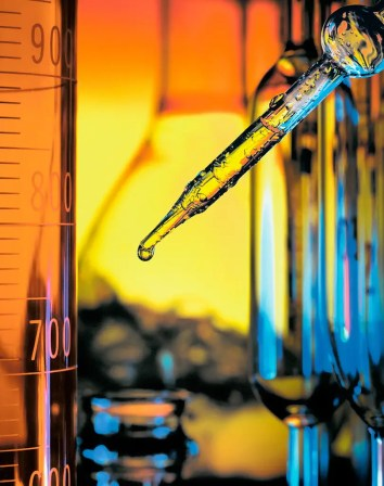Photograph of dropper and beakers in research laboratory - photo by Vancouver commercial photographer Robert Leon