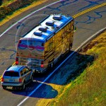 USA, a large motor home tows an SUV around a curve on a California highway