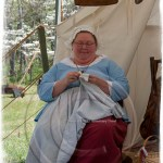 a woman dressed in colonial costume sits by her tent