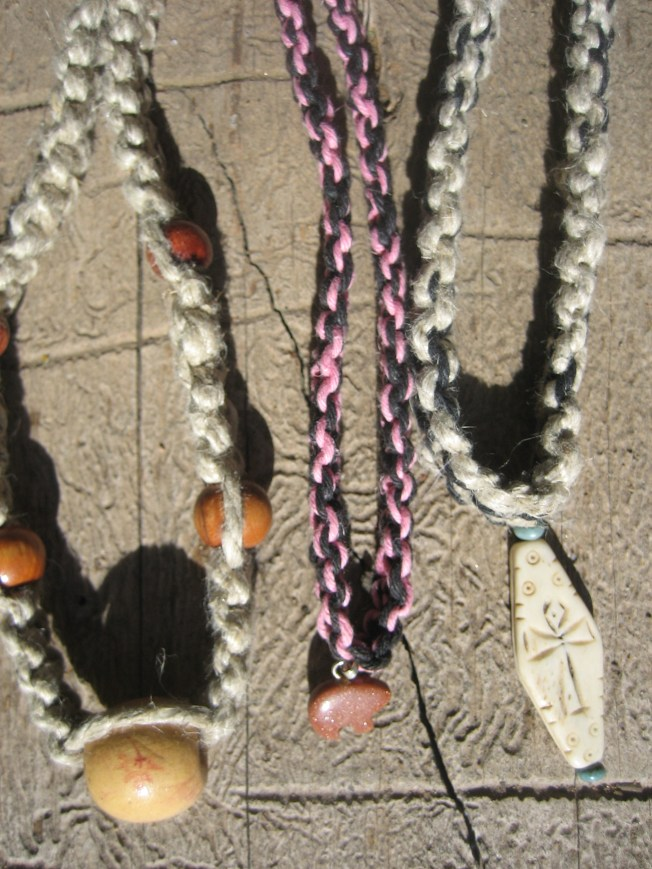 The necklace on the left is made from natural hemp and wooden beads. It is 21 inches long. It costs $11, including shipping. The middle necklaces features a goldstone bear on pink and black hemp. It is 14 inches long, and costs $11, including shipping. The necklace on the right is made from black and natural hemp. The carved bone pendant features an ankh. It is 20 inches long and costs $11, including shipping costs.