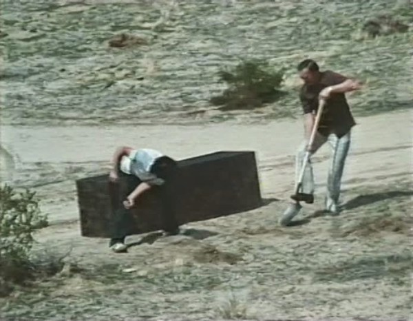 Two men bury an oblong crate in a shallow grave.
