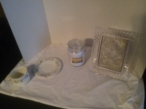 A set of tea cups and saucers, a scented candle, and picture frame