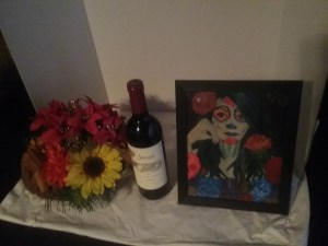 A swan wicker centerpiece, a bottle of high end wine, and a framed print of original art by Christine Stein