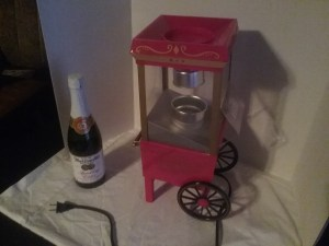 A tabletop popcorn machine and bottle of martinelli's sparkling cider