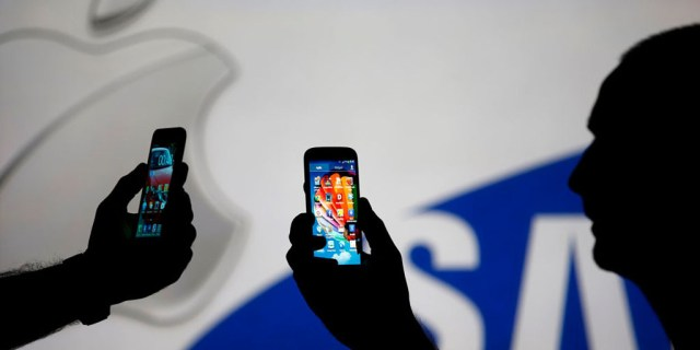 Men are silhouetted against a video screen with Apple and Samsung logos as he poses with Samsung S3 and Samsung S4 smartphones in this photo illustration taken in the central Bosnian town of Zenica, August 14, 2013. REUTERS/Dado Ruvic (BOSNIA AND HERZEGOVINA - Tags: BUSINESS TELECOMS) - RTX12L6W