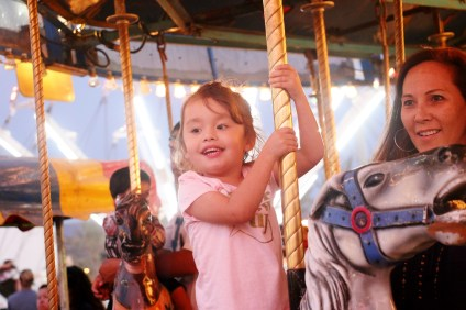 Darby Daniels, 3, rides the merry-go-round at Carnival Colossal on Sunday.