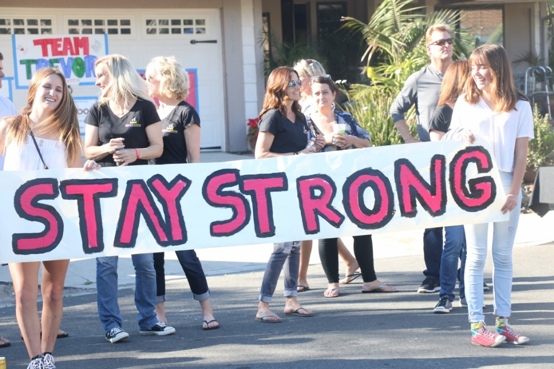 San Clemente High School students hold up signs with encouragement during a bedroom unveiling on Sunday, March 12, for their classmate Trevor Salman.