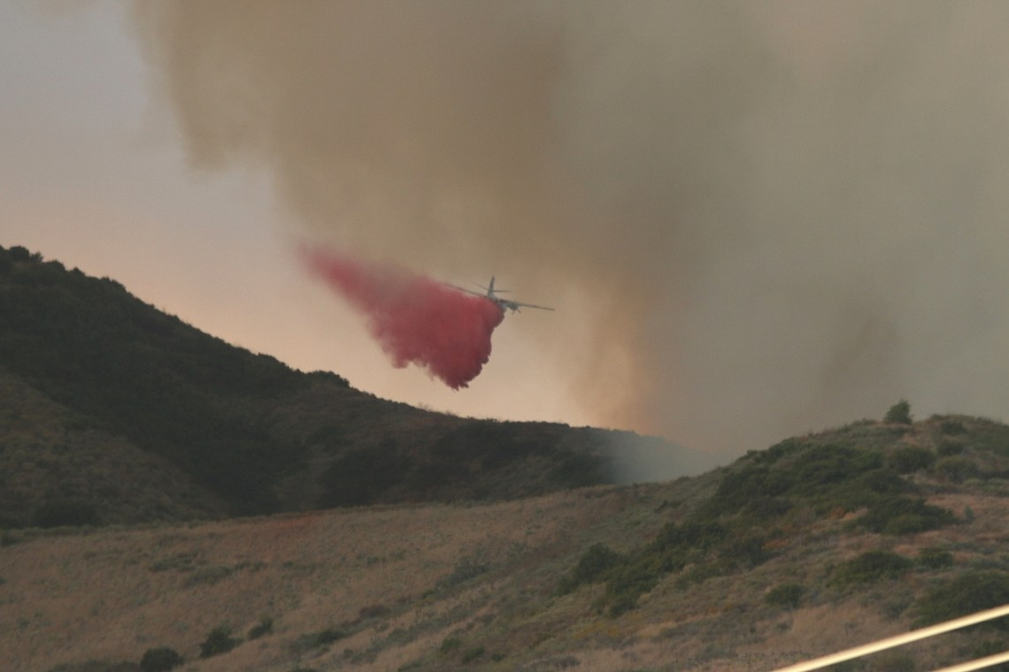 A Cal Fire plane drops fire suppression on a wildland fire located just south of San Clemente on Camp Pendleton on Wednesday, June 28. Photo: Eric Heinz